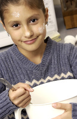 Girl stirring dough in a mixing bowl