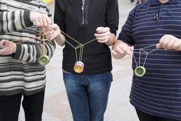 three teens with yo-yo toys in their hands. focus on yo-yo