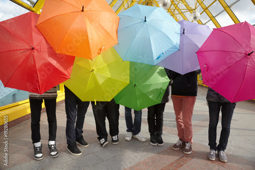 seven teens with opened umbrellas in pedestrian overpass