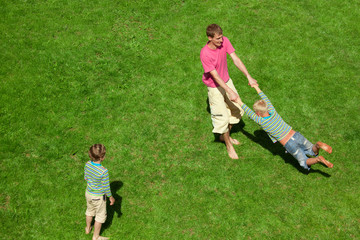Boys play with the man outdoor. The Top view.