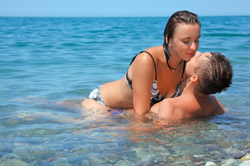 young hot woman sitting astride man in sea near coast, man and