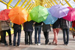 teens with umbrellas in pedestrian overpass. rainbow concept