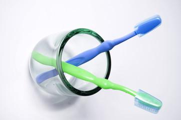 Cepillos de dientes en vaso de cristal