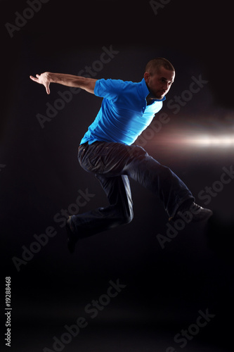 jumping cool man dancer against black background