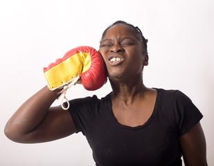 jeune femme noire se donne un coup gant de boxe