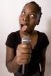 femme noire chante dans un micro avec emotion
