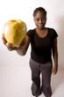 jeune femme noire tient une pomme jaune bio