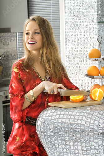 blonde in modern kitchen cuts oranges