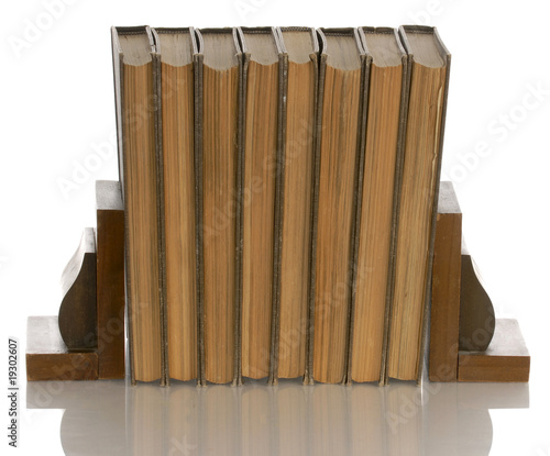 old books held up with wooden bookends with reflection