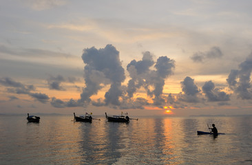 Thailand. Magic sunrise landscape with thai boats and kayaker