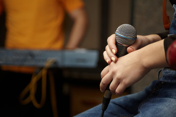 microphone in hand of girl. keyboard player in out of focus