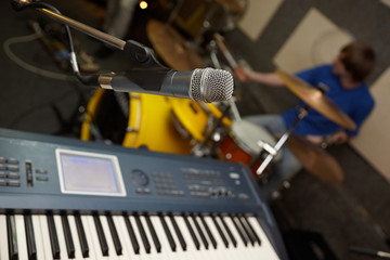 microphone near synthesizer. drummer in out of focus