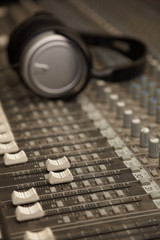 two faders of sound mixer in focus. headphones in out of focus