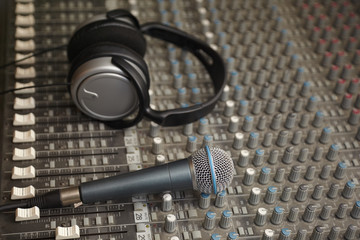 headphones and microphone on mixer pult. microphone in focus