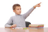 boy sits at a table. boy shows a finger on a subject poster