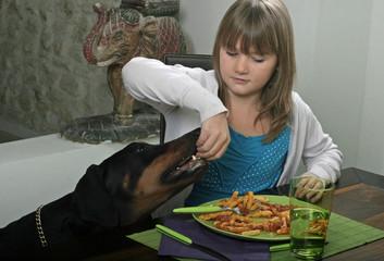 jeune fille partageant son repas à table avec son chien