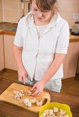 The girl cuts mushrooms
