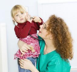 little girl at red hair female doctor founding stethoscope.