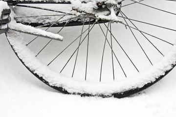 Bicycle wheel covered with snow in the Netherlands