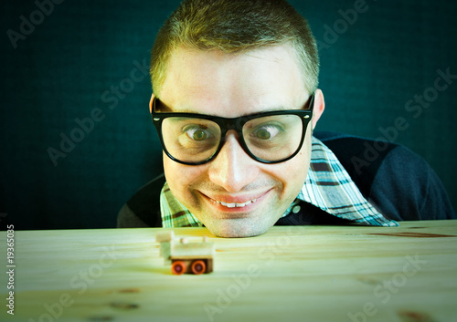 Funny nerd plays with small wooden train - focus on the face
