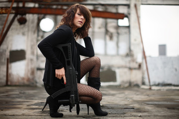 Young sexy woman in black with an assault gun.