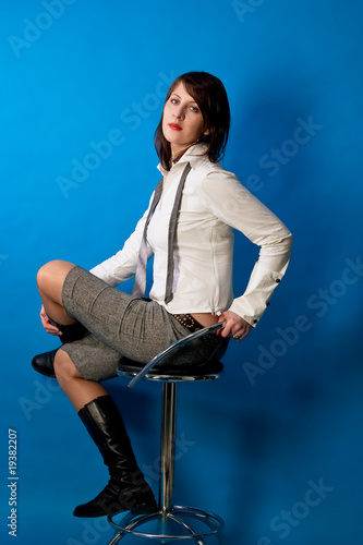 young relaxing dark haired girl in white shirt sitting on chair