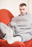 man with a broken leg on a sofa at home