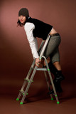 young tall girl in cap climbing on high ladder isolated