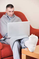 man with a broken leg on a sofa at home  working on laptop
