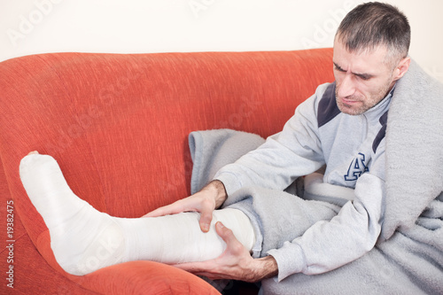 man with a broken leg on a sofa at home having pain