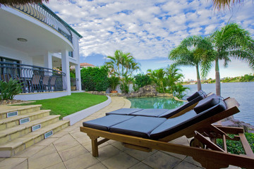 Deck chairs by the pool at waterfront mansion