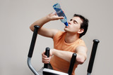 Boy on training apparatus drinks water in sportclub poster