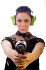Hübsche junge Frau mit Akkuschrauber und Gehörschutz