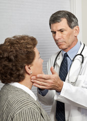 Doctor Checking Female Patient For Flu Symptoms in Office