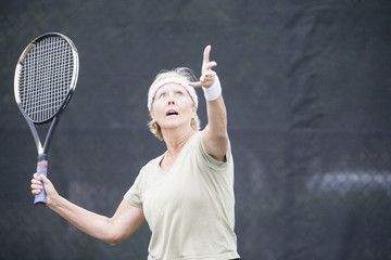 Senior woman serving at tennis
