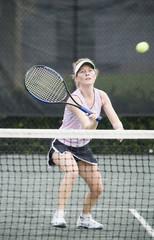 Mature woman hitting a tennis ball
