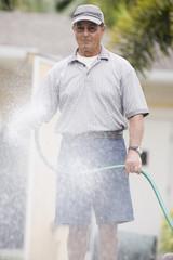 Senior man watering flowers