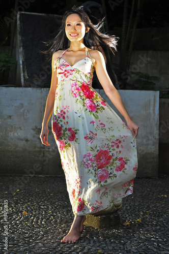 Pretty Asian Girl gliding past holding her dress