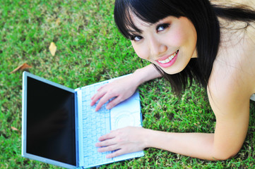 Pretty Chinese Girl accessing the computer in the park
