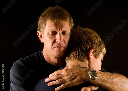 Leinwanddruck Bild emotional embrace - father hugging son