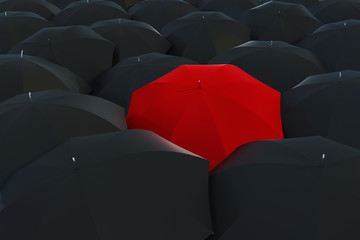 A single red umbrella surrounded by black umbrellas