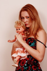 Sad young woman clutching doll