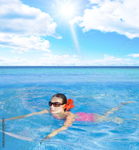 Woman in pink bikini and sunglassses swimming