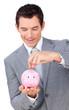 Smiling businessman saving money in a piggybank