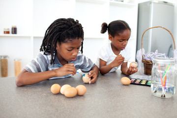 Concentrated Afro-american siblings painting eggs