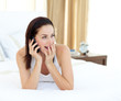 Surprised woman on phone lying on her bed
