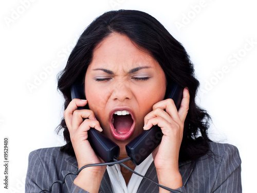 Frustrated businesswoman tangled up in phone wires