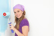 woman painting wall with roller in home