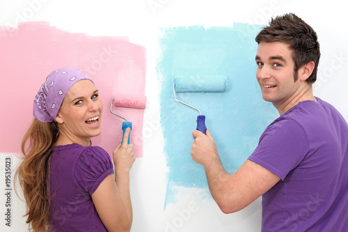 young couple painting and decorating new home