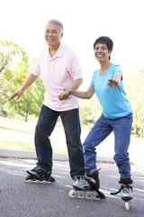 Senior Couple Skating In Park